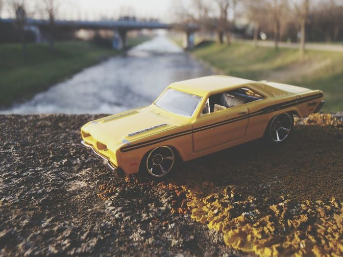 High angle view of yellow toy car on wall in front of canal