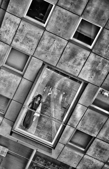 Reflection of man on glass window of building
