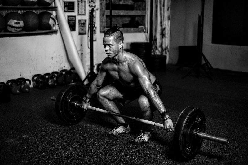 Portrait Of Man Lifting Barbell In Gym