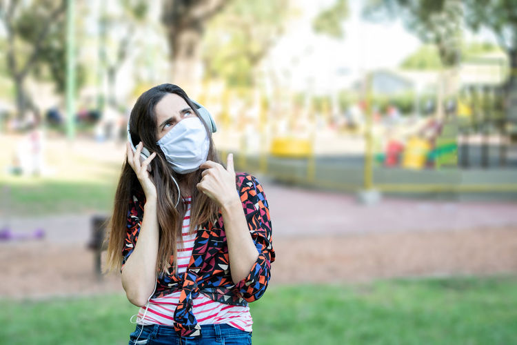 Woman wearing mask and headphones sitting at park