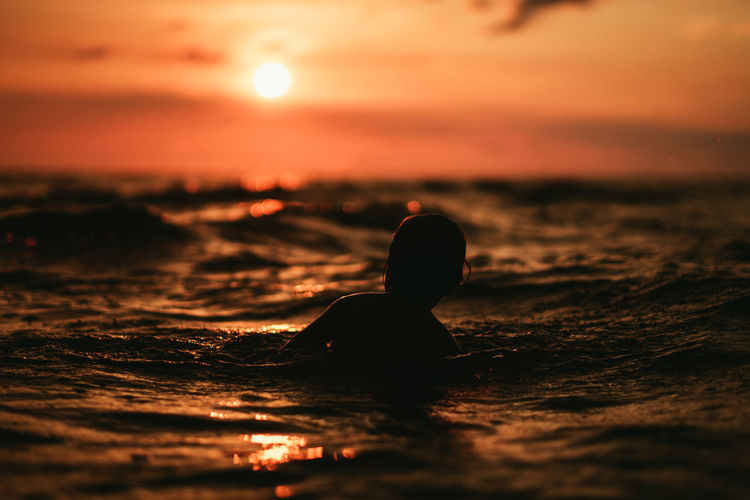 Silhouette person swimming in sea during sunset