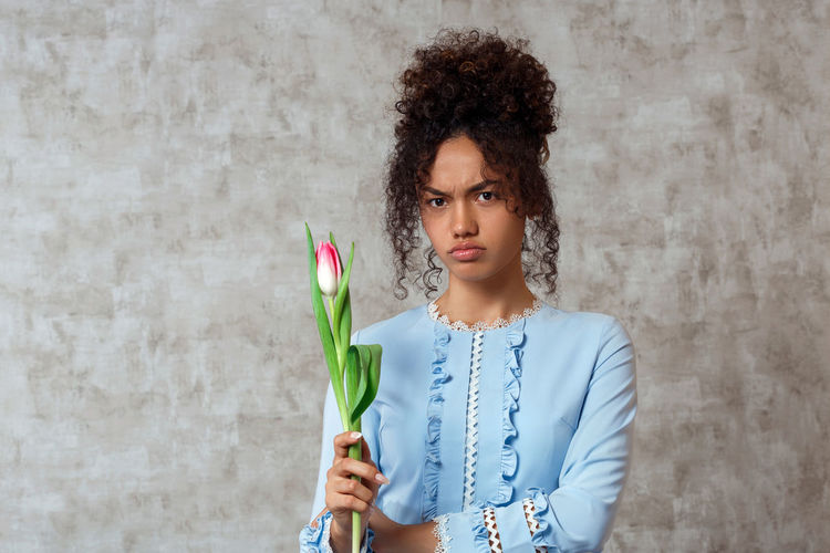 Portrait of young woman holding tulip while standing against wall