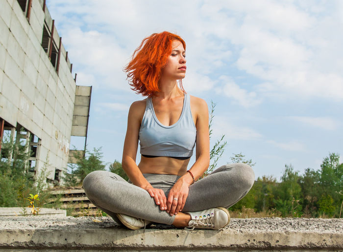 Beautiful girl sitting on the edge of the old gray slab Sitting One Person Young Adult Leisure Activity Real People Lifestyles Casual Clothing Young Women Women Day Hairstyle Outdoors Redhead Front View Full Length Cross-legged Adult Nature Sky Looking Beautiful Woman Old Ruin Ussr Postindustrial