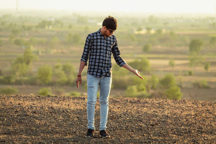 One Person Full Length Casual Clothing Real People Land Field Young Adult Lifestyles Standing Leisure Activity Young Men Focus On Foreground Nature Day Landscape Rural Scene Scenics - Nature Farm Non-urban Scene Outdoors Hairstyle Jeans