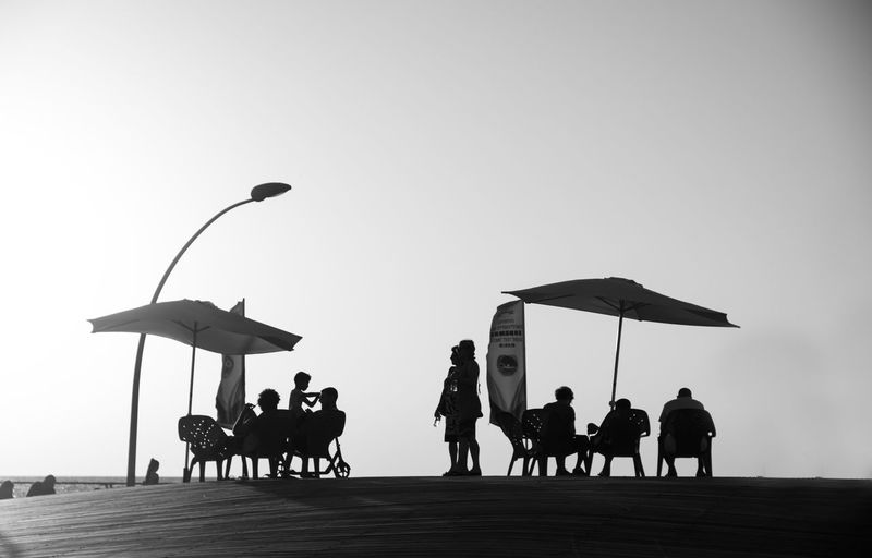 Silhouette Of People Relaxing At Beach