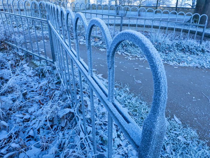High angle view of snow covered metal railing during winter