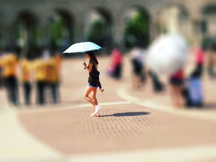 Tilt-shift image of woman holding umbrella while standing on street
