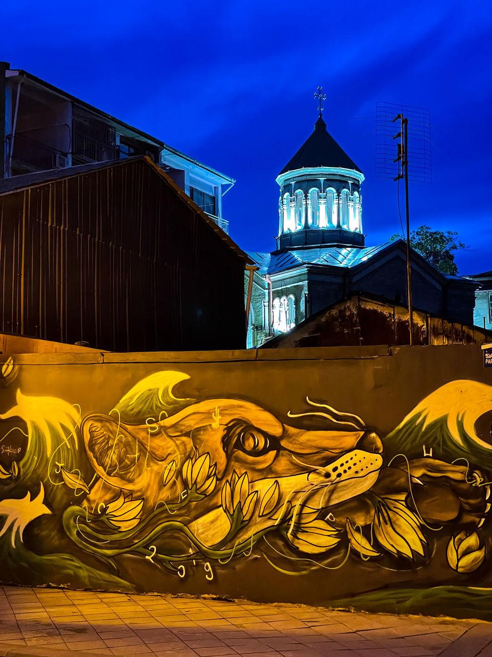 GRAFFITI ON ILLUMINATED BUILDING AT NIGHT