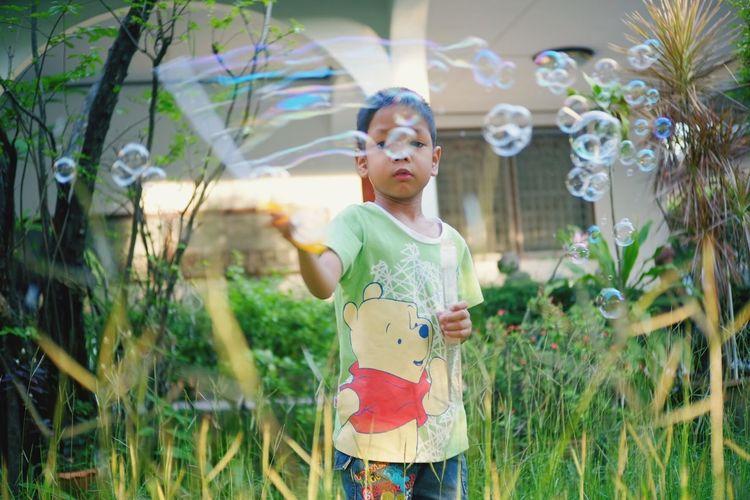 Full length of girl standing against plants