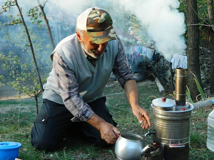 Mature man preparing food at campsite