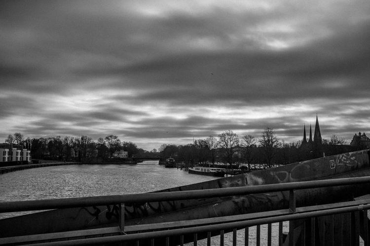 Bridge over river against sky in city