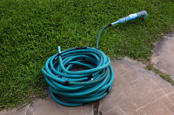 Cement Faucet Gardening Equipment Graden Grass Green Color No People Outdoors Row Rubber Hose