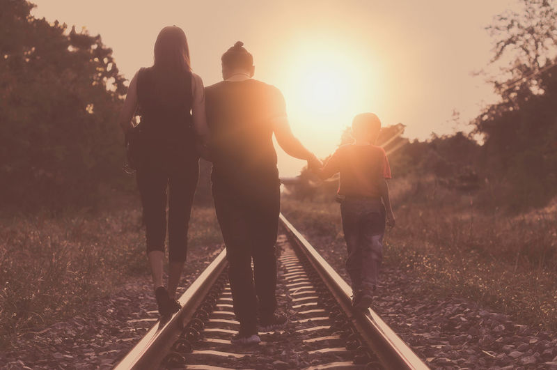 Rear View Of Family Walking On Railroad Track Against Sky During Sunset