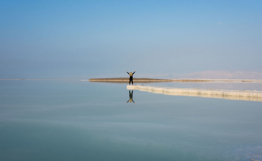 Woman in sea against clear sky
