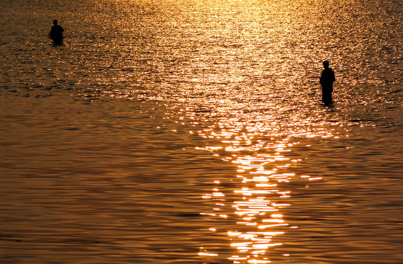 Silhouette fisherman fishing in sea during sunset