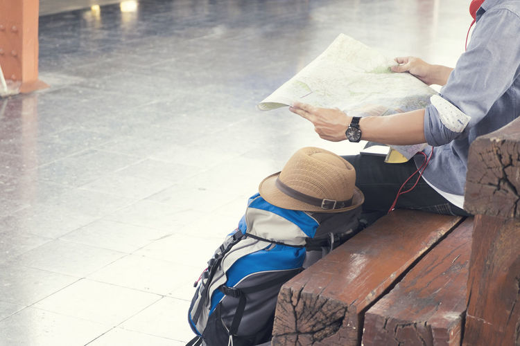 Midsection Of Man Reading Map While Sitting On Wooden Bench