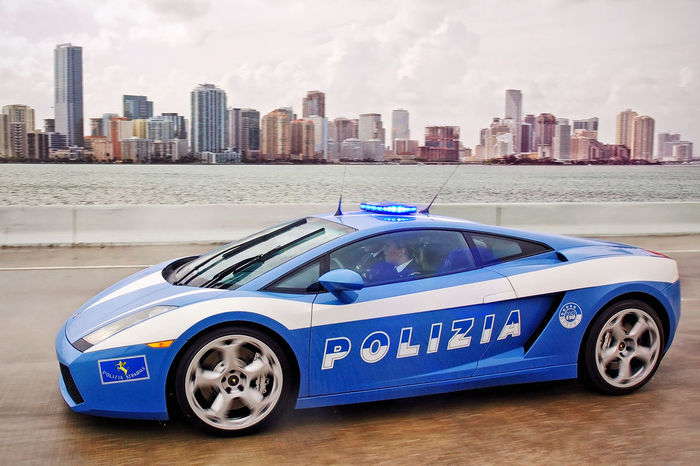Miami, USA - June 01, 2007: A special car of the Italian State Police plows through the streets of Miami on a rainy day. In the background the skyline of skyscrapers of the beautiful American city. Italian Automobile Car Divided Drive Driving FlashingLights Italy Lamborghini Miami Officers Police Policewoman Rain Road Skyscrapers In The Clouds Special Supercar Woman Agent Woman Cop