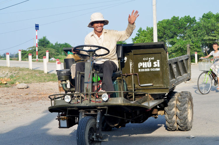 Happy guy on farm vehicle in village near Hoi An, Vietnam. Bicycles Bikes Boys Day Editorial  Happiness Hoi An Men Outdoors Rural Sitting Smiling Sun Hats Transportation Vehicles Vietnam Villages Waving Workers