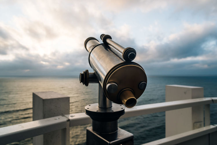 Close-up of telescope by sea against sky