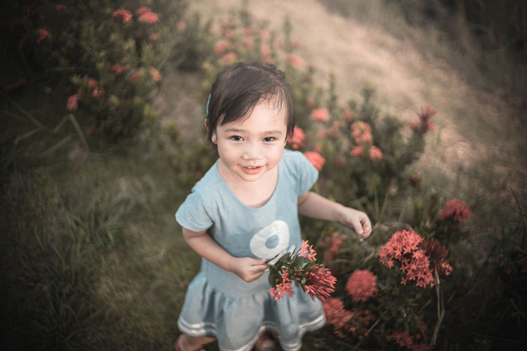 High angle portrait of smiling girl standing by ixora plant on field