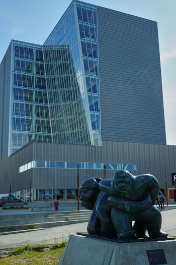 Statue of modern building in city against sky