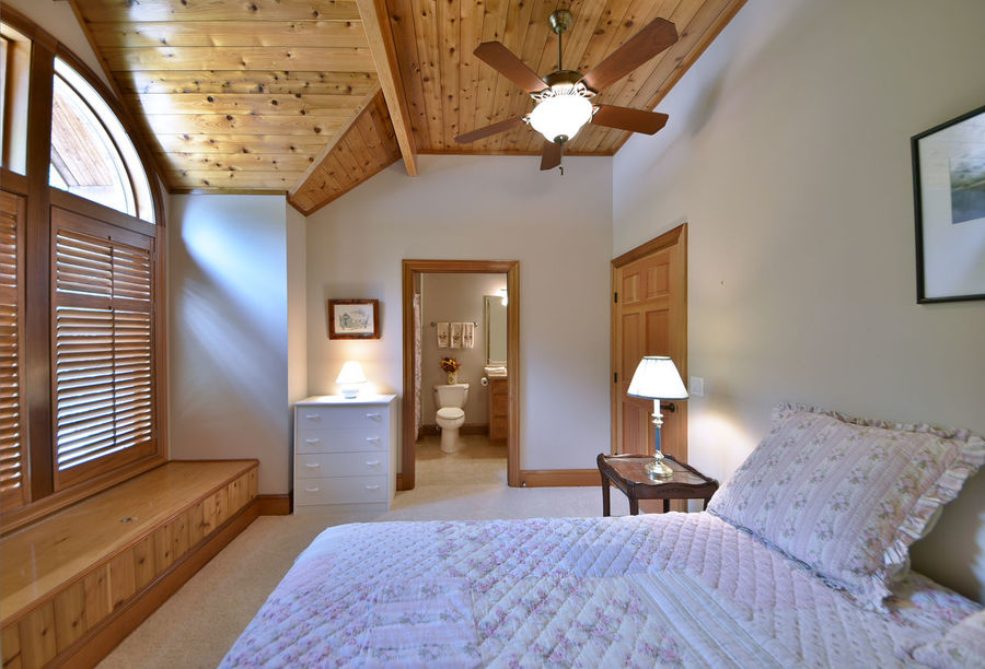 Retire in comfort to the luxurious master suite. Architecture Bed Bed & Breakfast Bedroom Ceiling Fan Day Domestic Life Guest Bedroom  Home Interior Home Showcase Interior Hotel Hotel Room Hotel Suite Illuminated Indoors  Log Cabin Luxury Luxury Hotel Master Suite No People Pillow Rustic Charm Wealth Window Wood Paneling