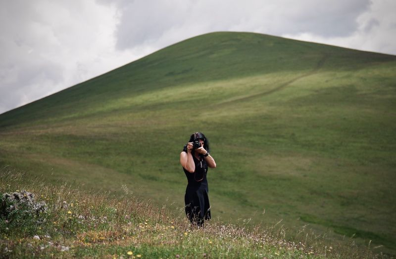 Full length of woman photographing on field