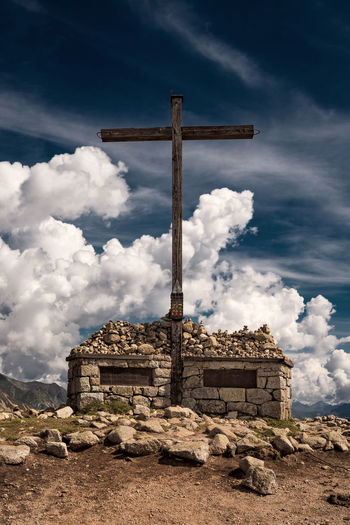 Cross and old ruin on mountain peak against cloudy sky
