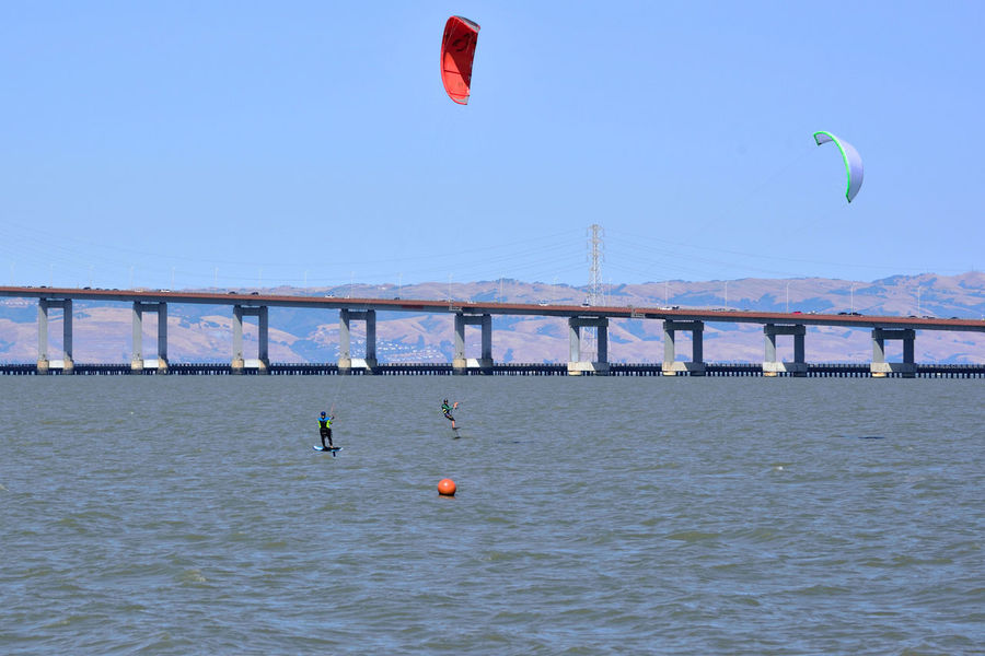 Kiteboarding In San Mateo 19 San Mateo, Ca. The Color Of Sport Kitesurfers Kiteboarding San Mateo Bridge Power Lines Power Towers Bridge Span Traffic On Bridge Colorful Sails Wind Power Watersports Aquactic Sports Sports Clear Blue Sky Calm Waters Course Marker Eastbay Hills San Francisco Bay Kitesurfing Leisure Activity Enjoying Life