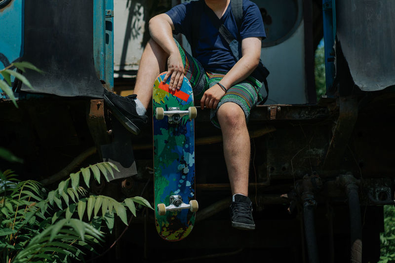 Low section of man sitting with skateboard on train
