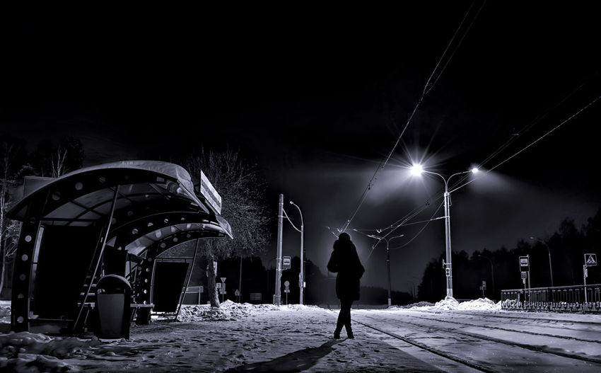 Silhouette woman waiting for tram during winter at night