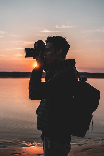 Side view of man photographing while standing at beach during sunset