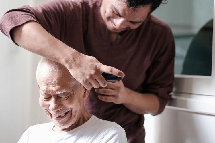 Smiling man cutting father hair