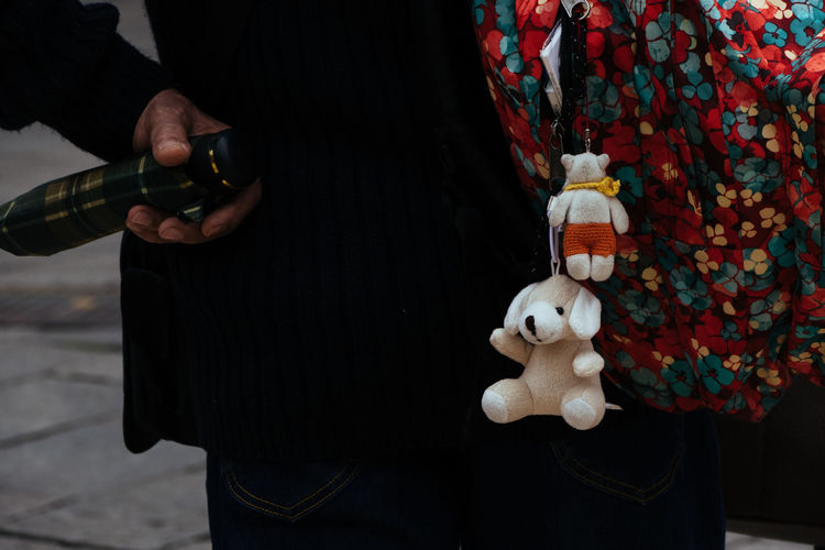 Teddy bears hanging from person bag