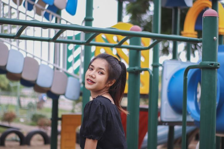 Portrait of smiling young woman standing in playground