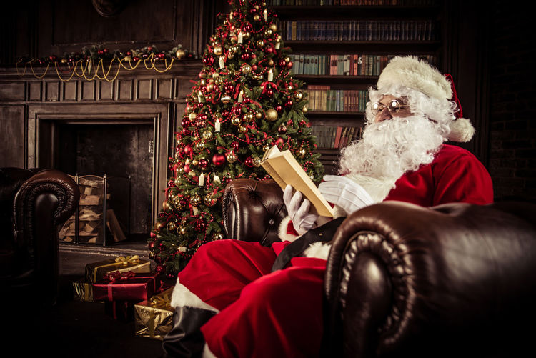 Man Wearing Santa Claus Costume Reading Book On Sofa At Home