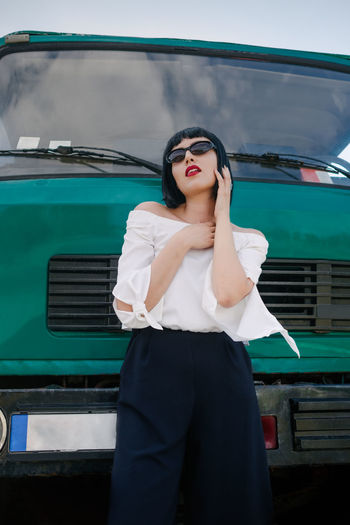 Young woman in sunglasses standing against truck