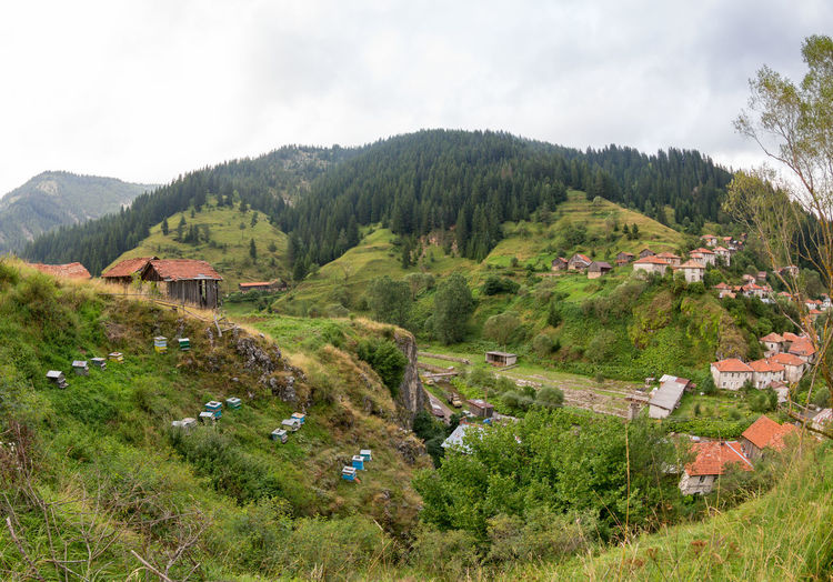 Scenic view of village by mountain against sky