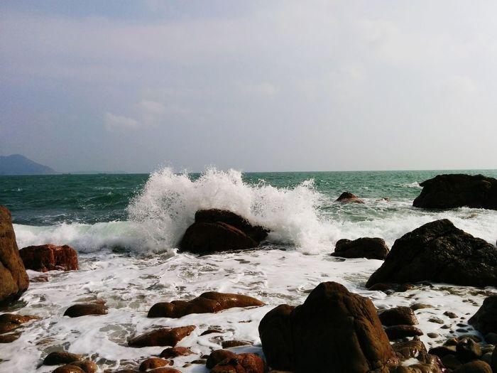 Waves splashing on rocks in sea against sky