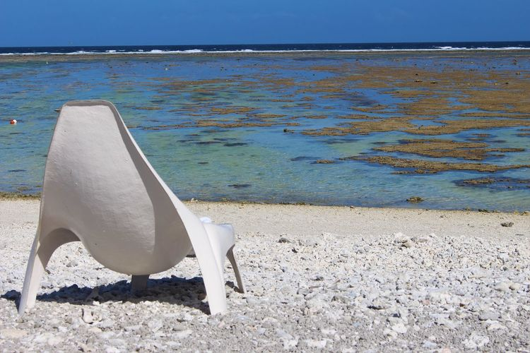 Deck chairs on shore at beach against sky