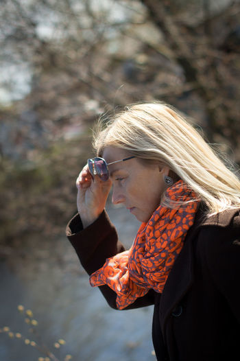 Woman wearing sunglasses looking at lake