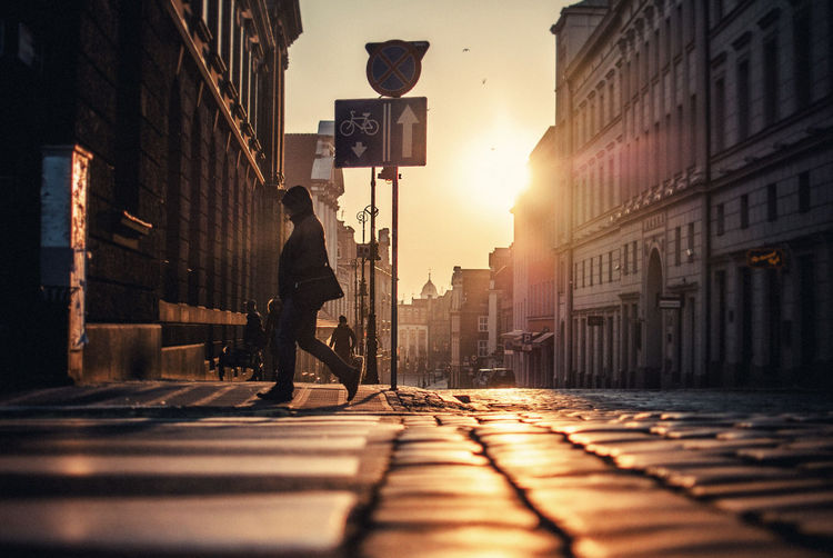 Side view of woman walking on street during sunrise