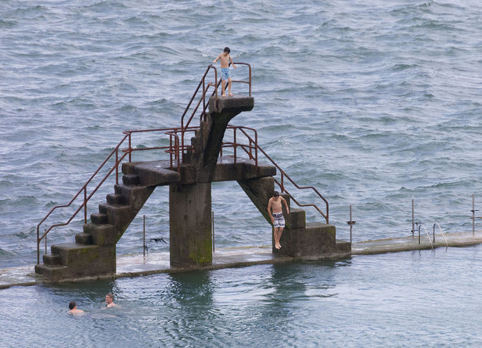 Teenage boy jumping into seawater pool in Saint-Malo, France Aquatic Atlantic Ocean Board Challenge Competition Courage Diving Board Diving Platform Jump Jumping Mid-air Platform Pool Sea Seawater Pool Sport Swimming Swimming Pool Swimwear Teen Teenage Boys Teenager Training Water Young Adult