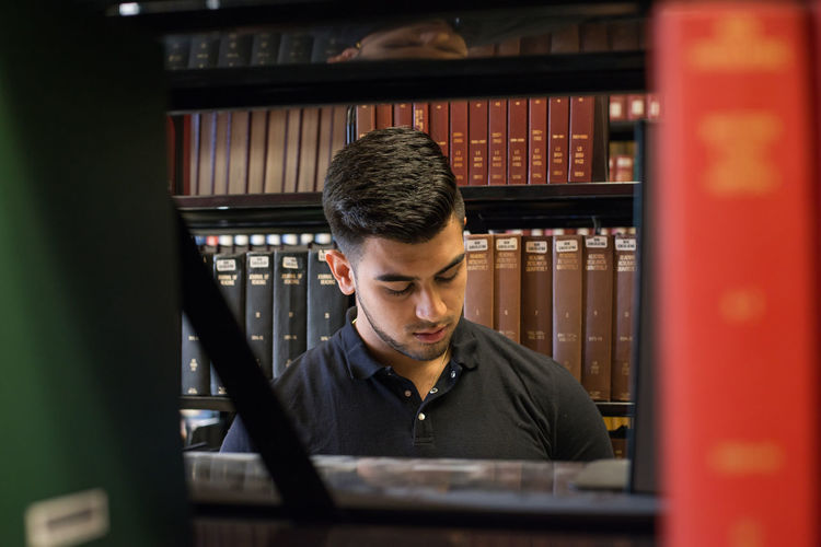Young Man Seen Through Bookshelves At College Library