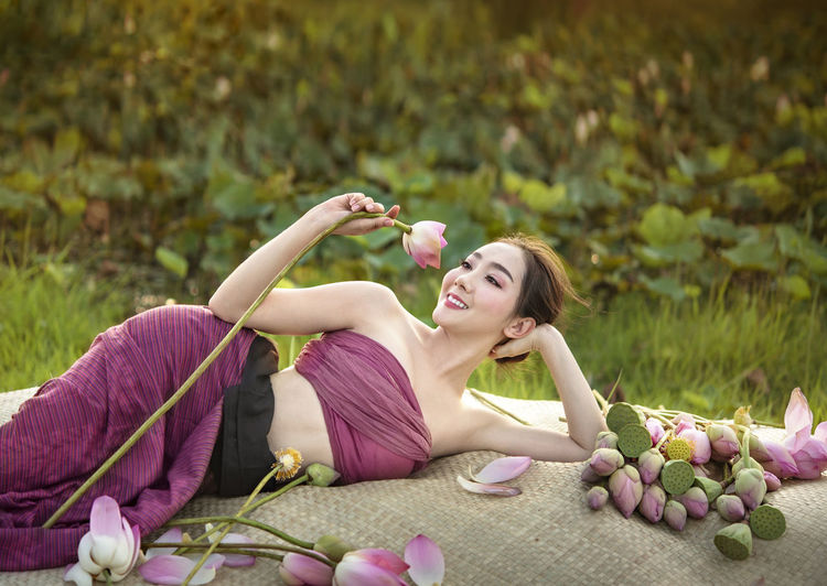 Beautiful woman resting on textile with lotus flowers on land