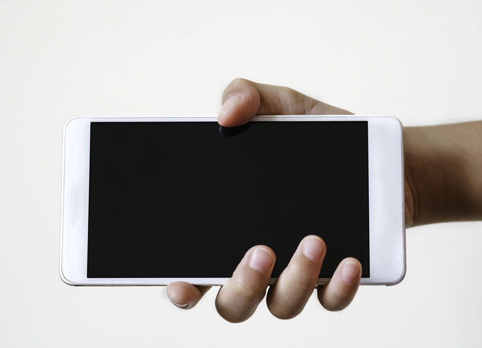 Hand holding smart phone over white background