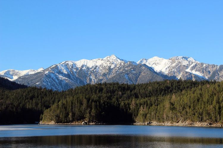 Lake by trees and mountains against clear sky