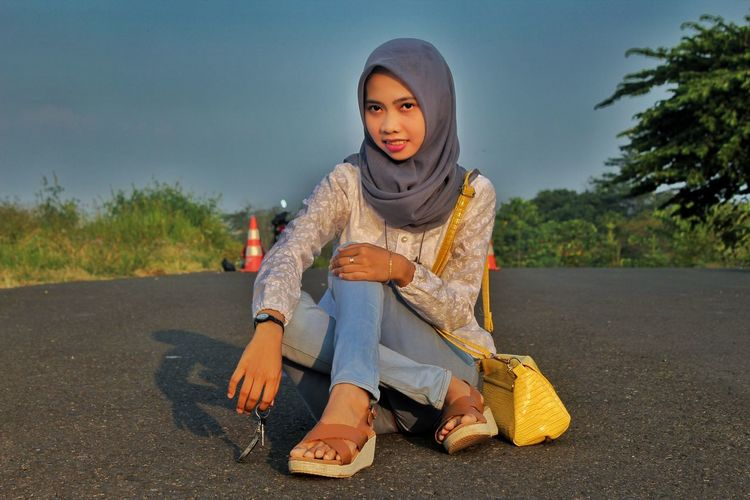 Portrait of young woman sitting on road against trees