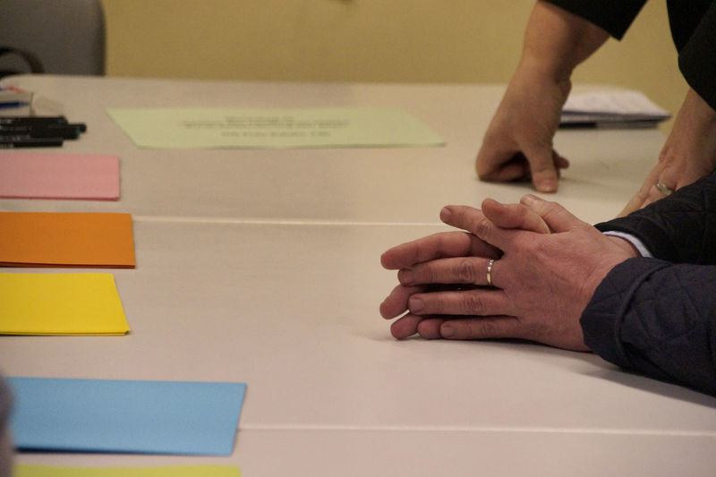 Close-up of people hands on table with colorful papers