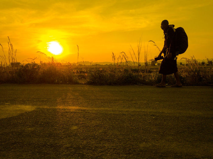 Man photographing on field during sunset